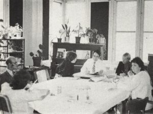 black and white photo of group of people meeting around table, circa 1970s