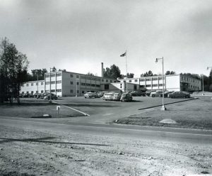 Low-raise institutional building with vintage 1960s cars parked in front