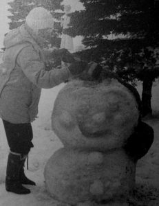 old black and white photo of person in winter clothes standing next to snow sculpture