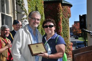 man and woman standing smiling in front of buildng holding award plaque