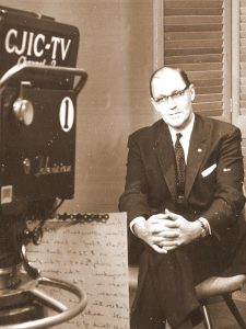 old black and white photo of man in suit facing television camera, 1950s look