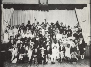 black and white group photograph of approx 100 adults dressed in costumes