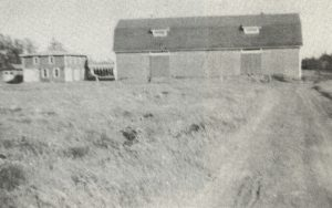 old black and white photo of barn and field