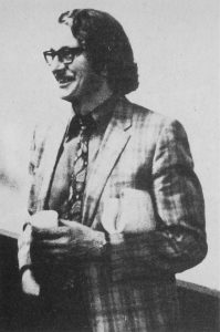 Man with mustache, glasses and 1970s style suit and tie