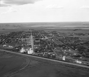black and white photo of typical small prairie town with grain elevators