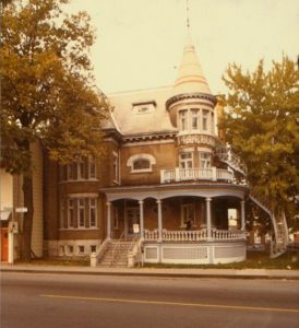 old colour photo of elaborate brick residential home
