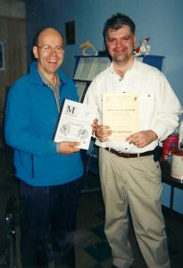two smiling men standing next to each other holding publications