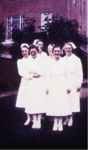 old photo of a group of nurses in uniform in front of brick building