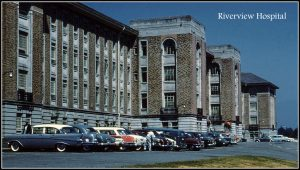imposing entrance to stone or brick institutional building, 1950s cars parked out front