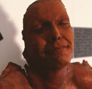 photo of red woman sculpture, face and shoulders and UNLADYLIKE stamped across chest