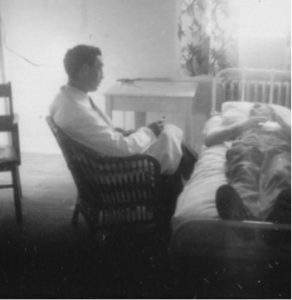 old black and white photo of man in white lab coat sitting on chair talking to patient in bed