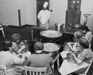 Photo en noir et blanc d'un chef cuisinier enseignant à un groupe de femmes dans une cuisine