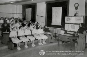 old black and white photograph of uniformed nurses in classroom being instructed by nun in front of room
