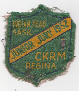small green badge with torn edges and yellow text reading Junior Jury 1952