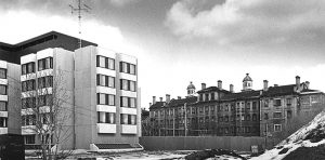1970s black and white photo showing modern institutional building on the left and old 19th century institutional structure on the right