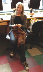 colour photo of smiling young woman with long blond hair sitting in office chair knitting