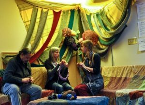 colour photo of people on couch knitting, furniture and skylight are draped with beautiful coloured fabric