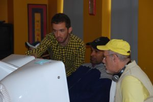 colour photo of 3 men looking at computer screen