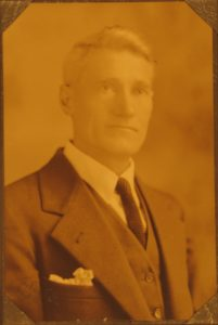 white haired man in an old fashioned suit and tie