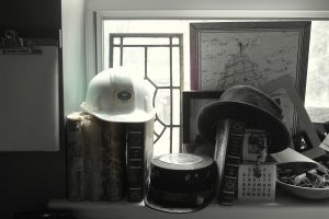 photo of assorted hats, books, art on office window sill