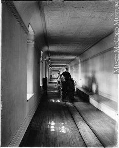 Long corridor étroit au centre duquel il y a un wagon de train électrique conduit par un homme