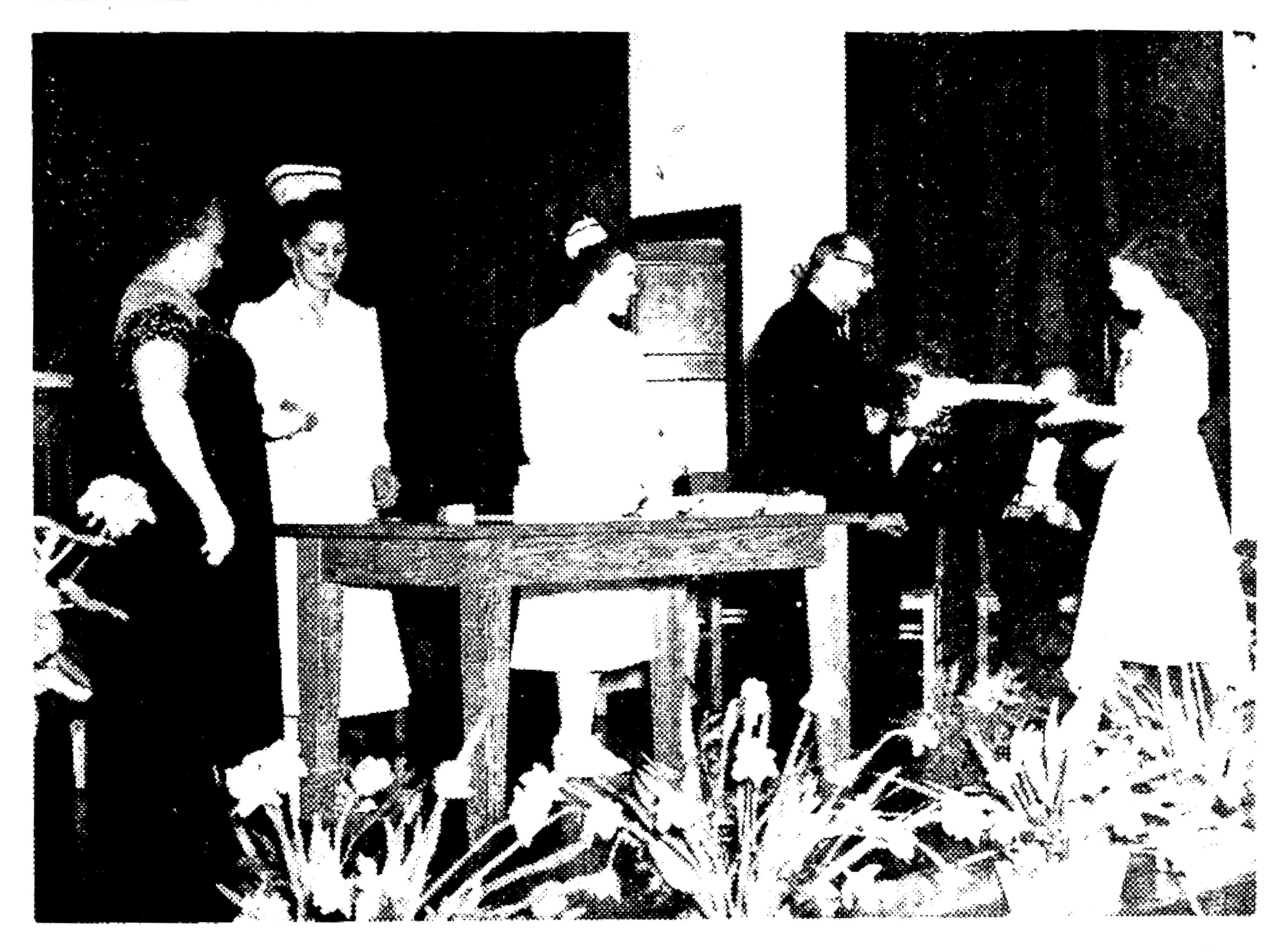 old black and white photo of nursing graduation scene with student receiving diploma on stage