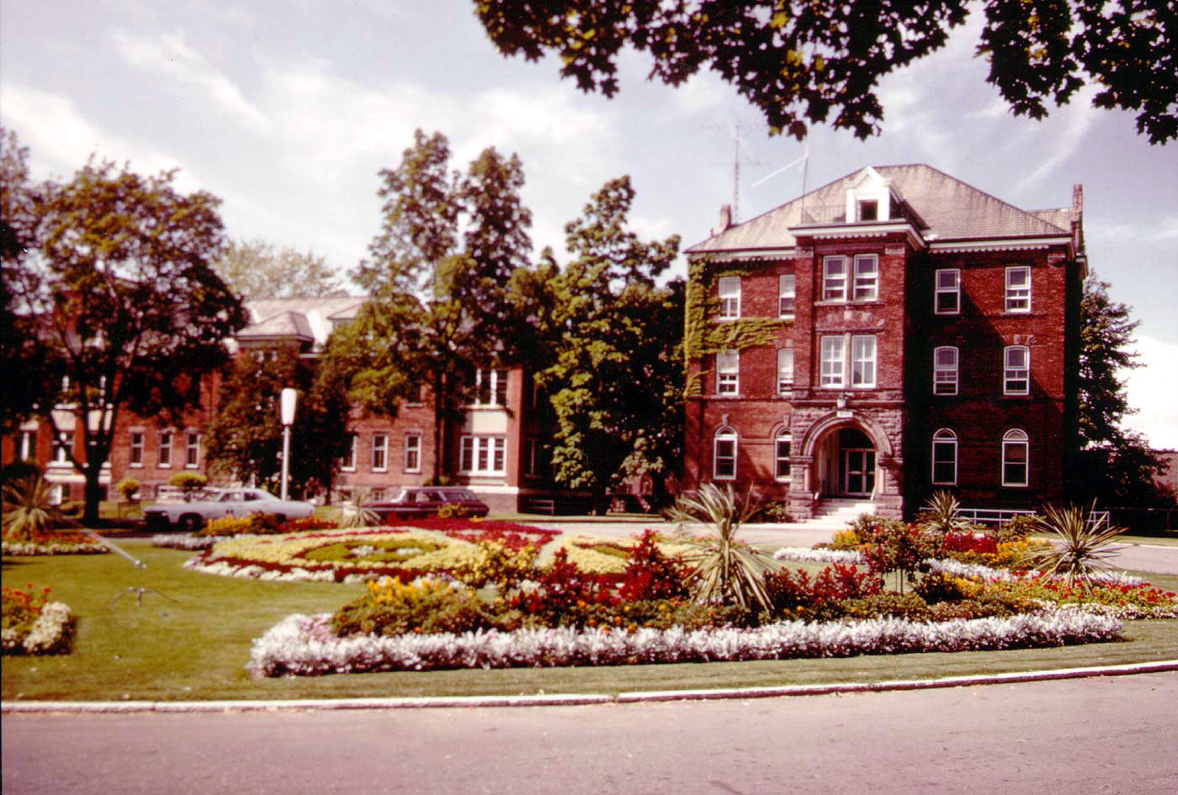 old brick institutional building with flower gardens in front