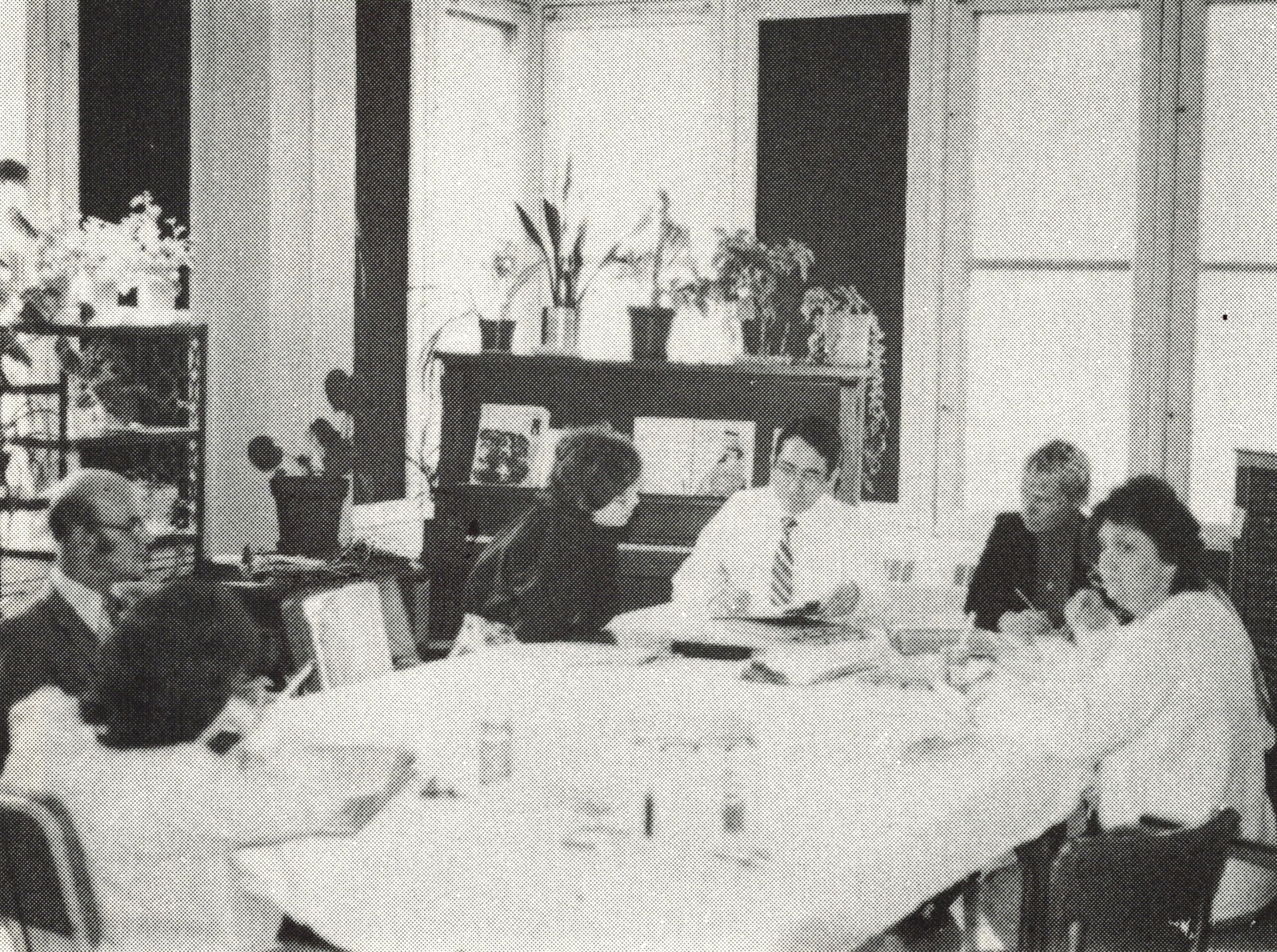 Photo en noir et blanc d'un groupe d'hommes et de femmes réunis autour d'une table