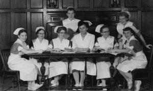 Ancienne photo en noir et blanc d'un groupe de femmes en uniforme d'infirmières souriant autour d'une table