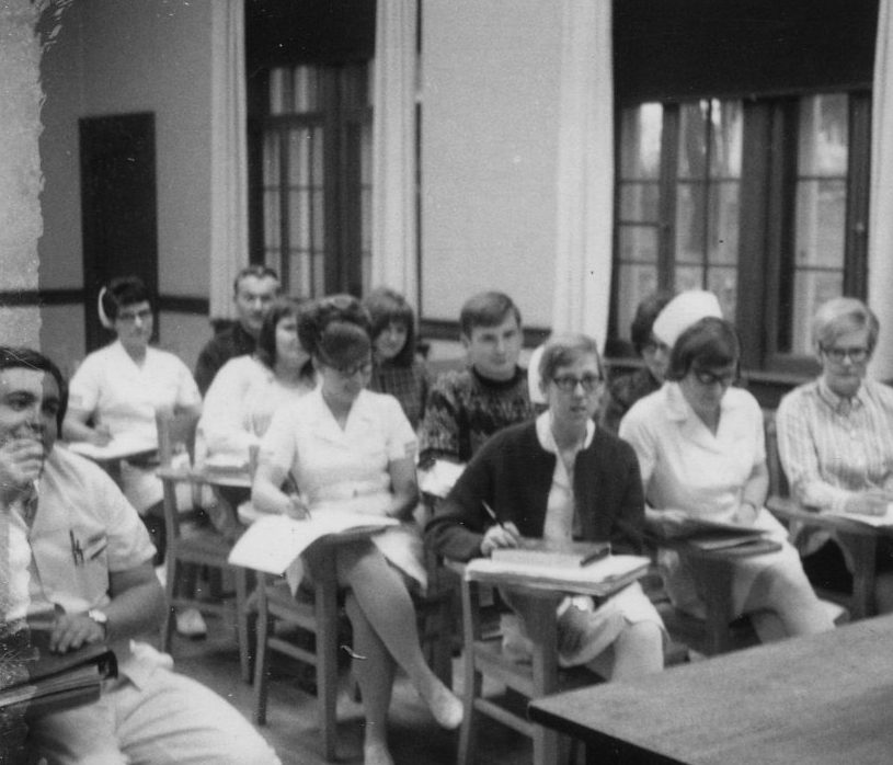 old 1960s black and white photo of nursing students sitting at desks in class with instructor in front