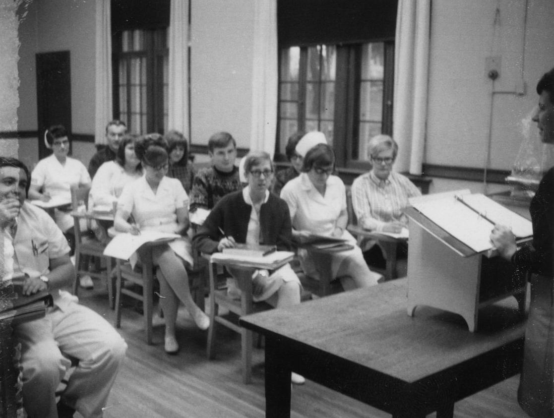 étudiants en soins infirmiers assis à des bureaux en classe avec instructeur