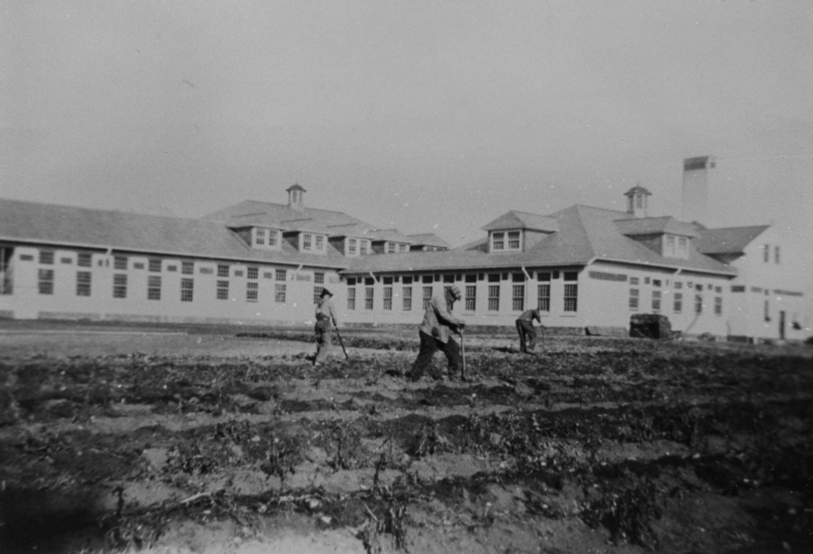 old photo of men working in fields with institutional building behind