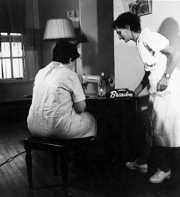 Ancienne photo en noir et blanc d'une femme assise devant une machine à coudre et une autre femme debout à sa droite qui l'assiste
