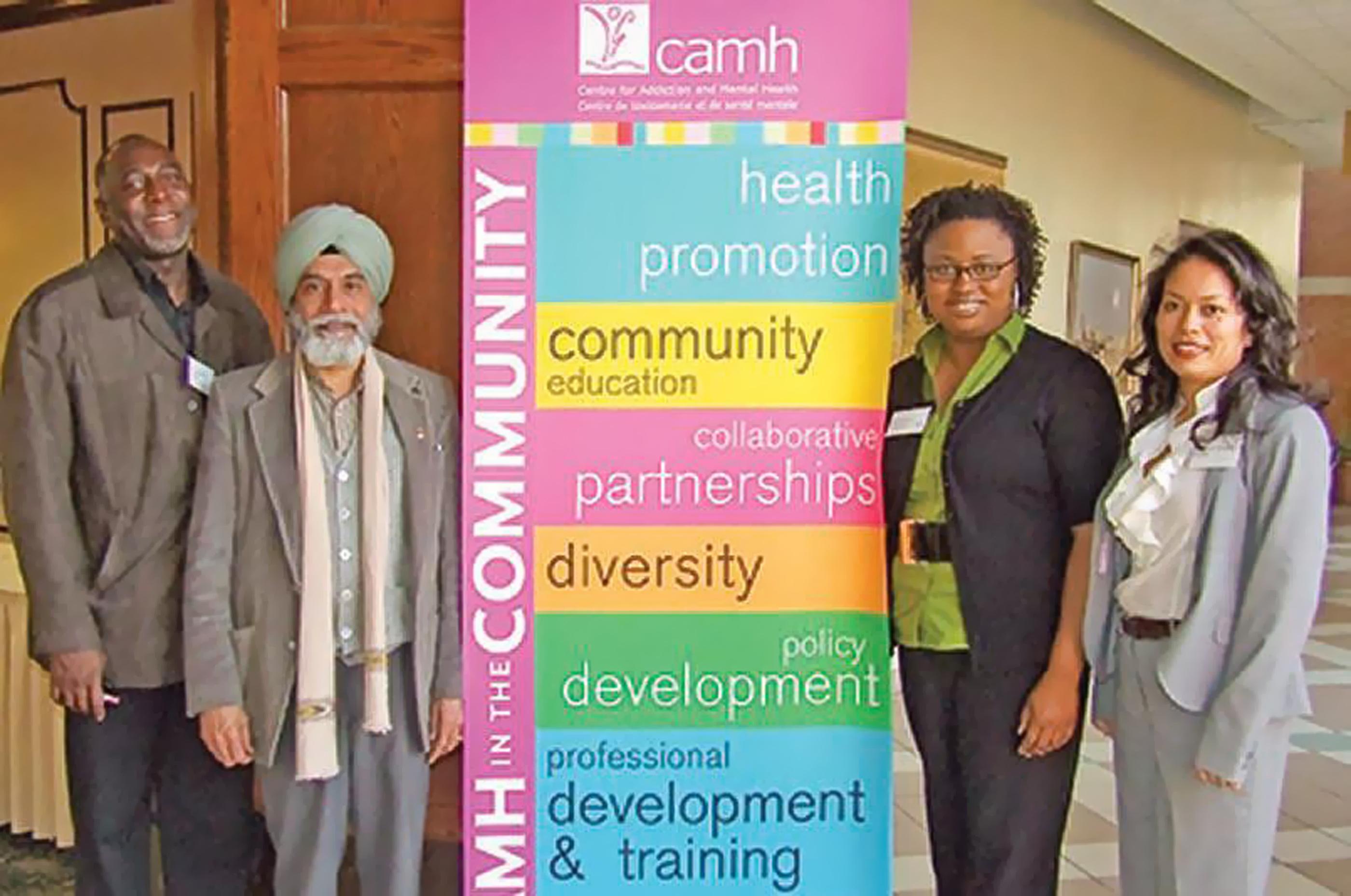 Photographie en couleurs représentants quatre membres de minorités visibles avec une affiche du CAMH au centre