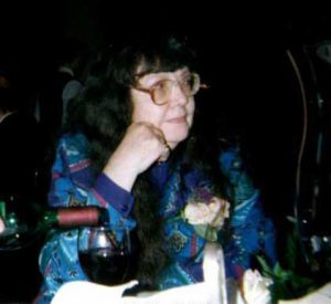 middle-aged woman with glasses and dark hair seated at dinner table