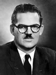 1950s black and white photot of man with dark hair, mustache, glasses where a jacket and a tie.