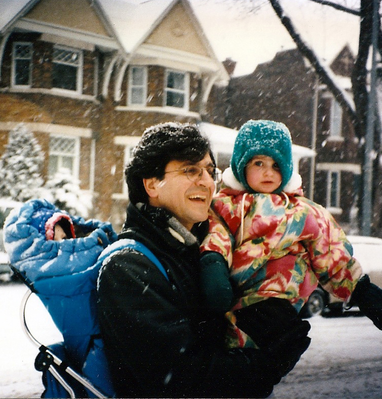 man holding baby on snowy street