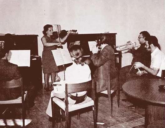 Photo en noir et blanc d'un groupe d'hommes et de femmes jouant divers instruments de musique