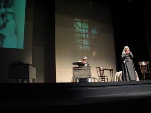stage performance with woman with long white hair and grey dress standing to stage right and woman with nurse's cap sitting at desk with typewriter