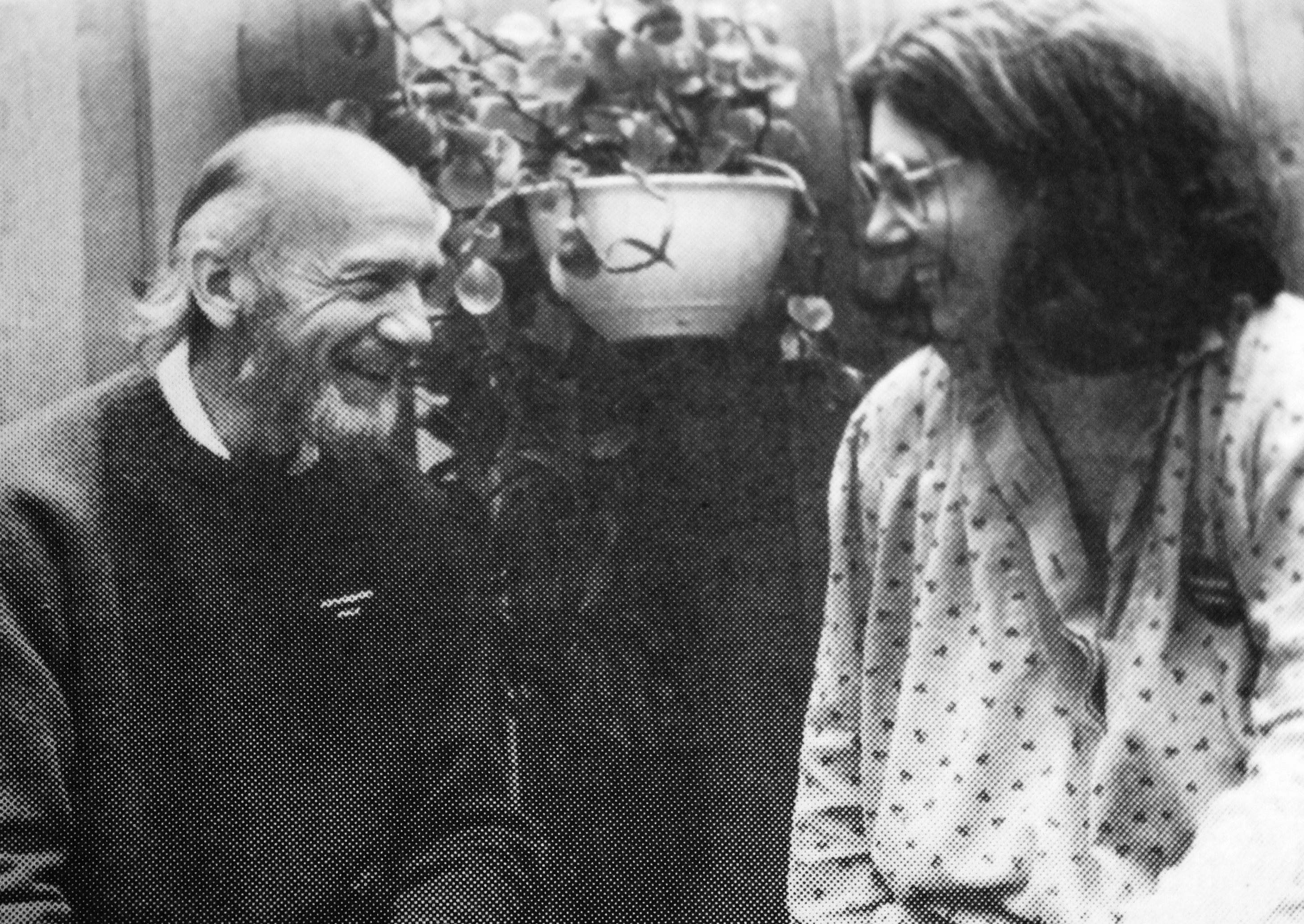 balding bearded man on left and dark haired woman with glasses on right