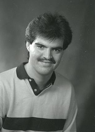 Photo en noir et blanc d'un jeune homme souriant