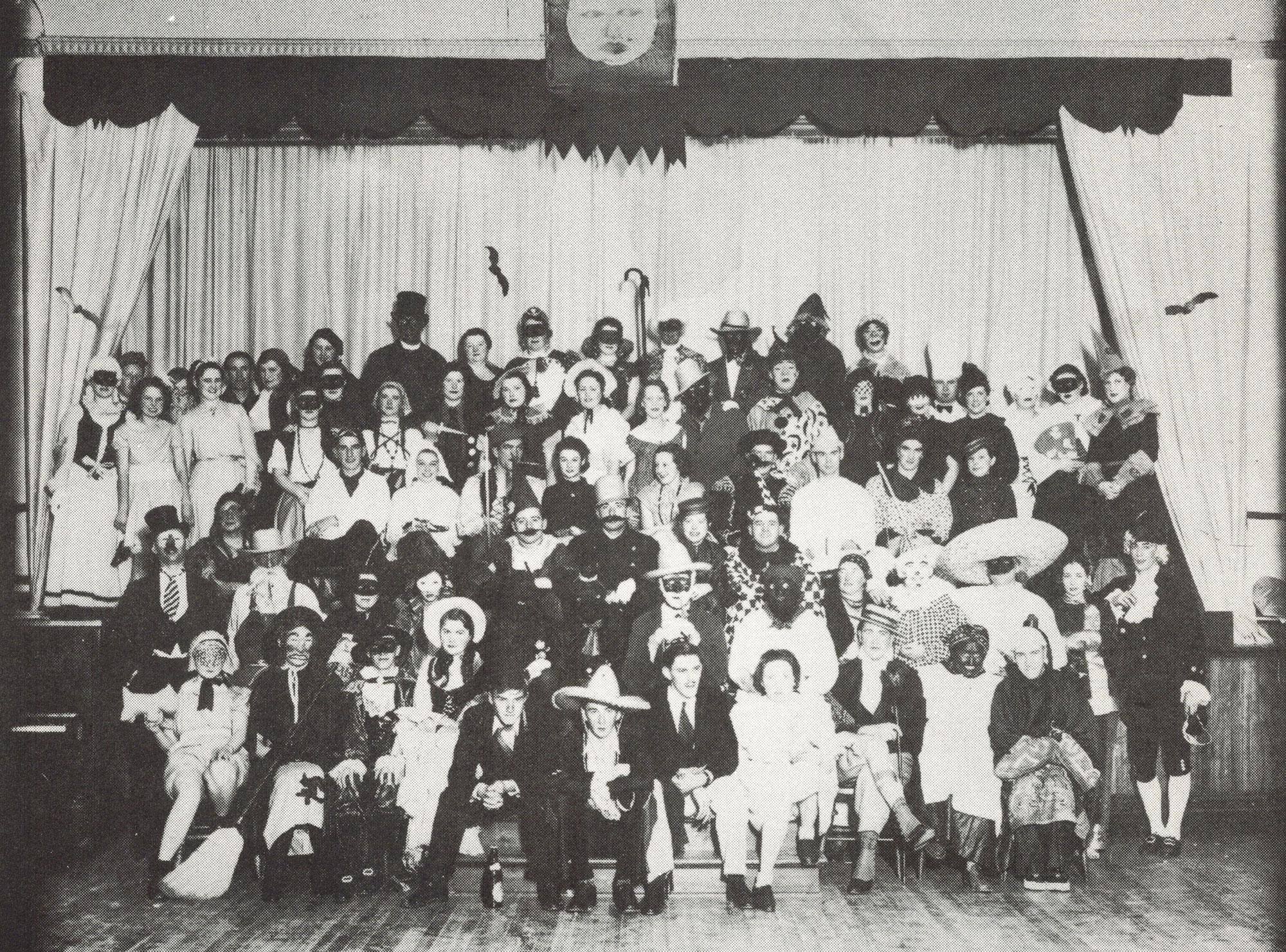 Photo en noir et blanc d'environ une centaine d'hommes et de femmes déguisés