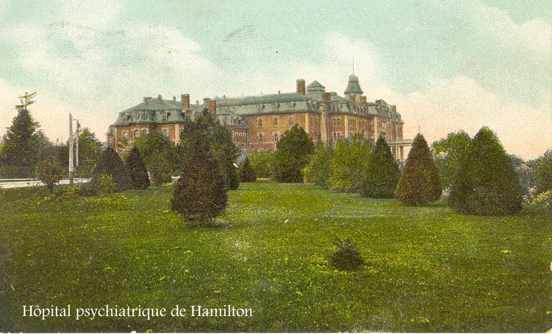 Imposant édifice ancien, en brique, au sommet d'une colline avec des arbustes et de l'herbe en face