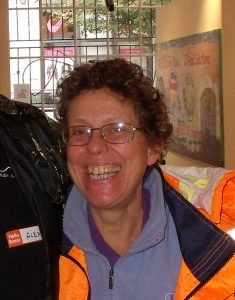 smiling middle-aged woman with glasses and short curly hair