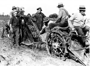 old photo of men working farm equipment