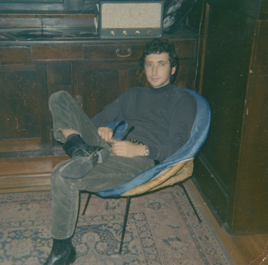 Young man with dark hair and trendy clothing sitting in chair