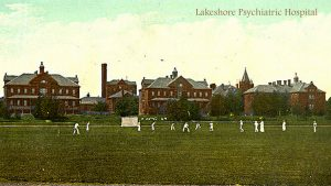 old coloured photograph of series of larger old brick residential buildings, field and cricket game in front