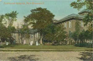 image of old stone wing of large building, female figures in long white dresses, lawn, trees and driveway in front