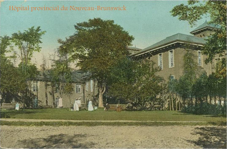 Ancienne photo en couleurs représentant un vieil édifice institutionnel en pierre entouré d'arbres avec des femmes en longues robes blanches sur le terrain devant