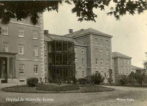 Photo en noir et blanc d'une aile d'un bâtiment institutionnel, avec une allée et un jardin devant